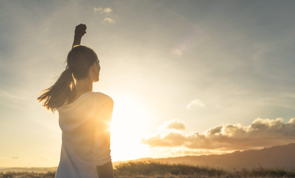 positive attitude woman holding fist toward the sun